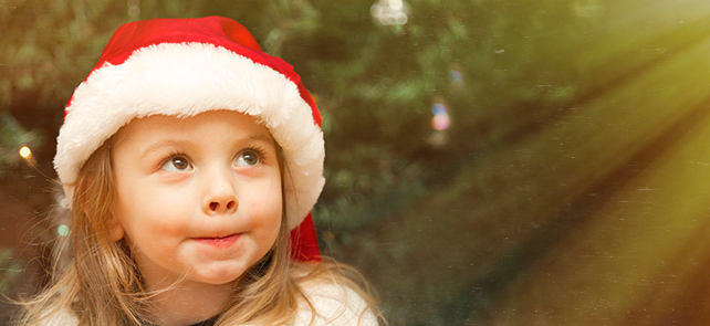 Adorable smiling little girl wearing red santa claus hat in front of the christmas tree